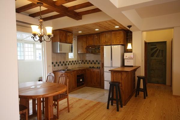 鄉村風的空間設計,一直是許多人的最愛,而在鄉村風的設計之中廚房最能凸顯鄉村風空間的異國情調。擁有多年豐富設計經驗,擅長鄉村風設計的原木工坊李佳鈺設計師,對於打造手感異國風鄉村風廚房,有其獨到的設計,透過不同的色彩搭配,以及巧妙的手工藝術拼貼,讓每個廚房展現與眾不同的個人特質。 換門片,就能讓廚具變成鄉村風 嶄新的現代廚具,如果為了呼應鄉村風而替換,太過浪費,也不環保,李佳鈺設計師將廚房的門片換成松木實木染白的門片,並且增設一個吧台區,松木染綠的檯面與天花板木樑、壁面的鄉村風層架相互呼應,白色櫃身則與門片採